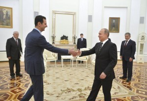 Russian President Putin shakes hands with Syrian President Assad during a meeting at the Kremlin in Moscow