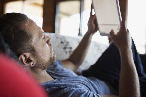 Man laying on sofa using digital tablet